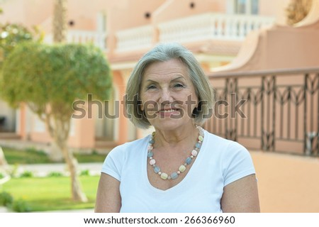 Portrait of a senior woman on a walk in tropic resort - stock photo