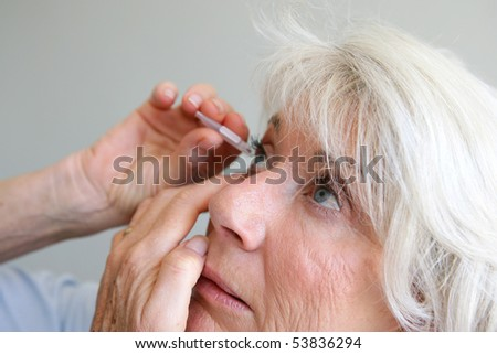 Portrait of a senior woman putting itself drops in her eyes - stock photo
