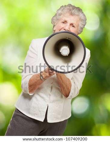 portrait of a senior woman screaming with a megaphone against a nature background - stock photo