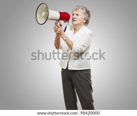 portrait of a senior woman shouting through a megaphone against a grey background