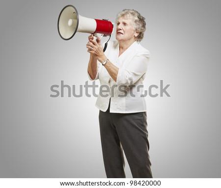portrait of a senior woman shouting through a megaphone against a grey background - stock photo