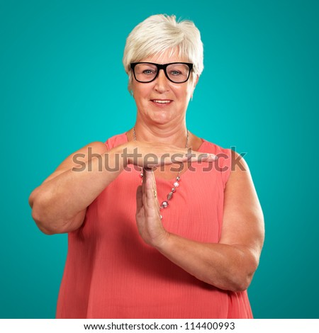 Portrait Of A Senior Woman Showing Time Out Signal On A Turquoise Background