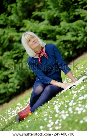 Portrait of a senior woman sitting in the grass reading a book - stock photo