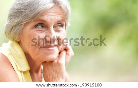 Portrait of a senior woman sitting outdors in summer - stock photo