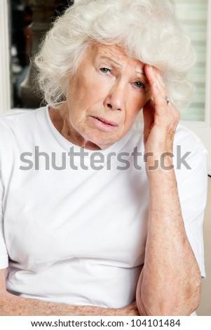 Portrait of a senior woman suffering from headache - stock photo