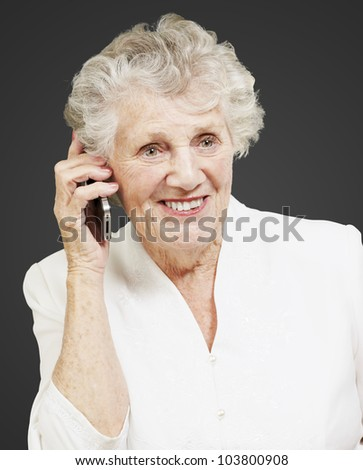portrait of a senior woman talking on a mobile over a black background - stock photo
