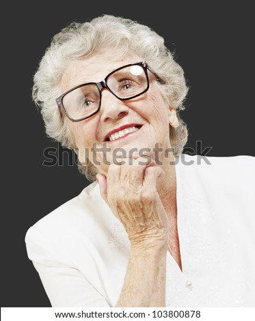 portrait of a senior woman thinking and looking up over a black background - stock photo