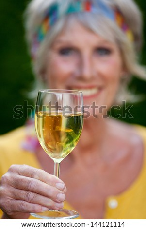 portrait of a senior woman toasting with wineglass
