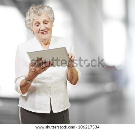 portrait of a senior woman touching a digital tablet, indoor - stock photo