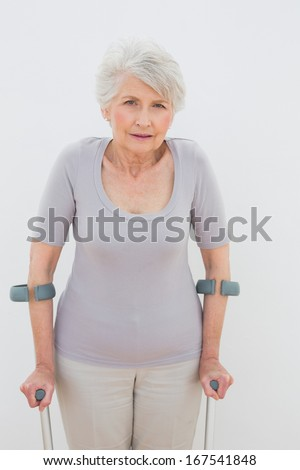Portrait of a senior woman with crutches standing against white background - stock photo