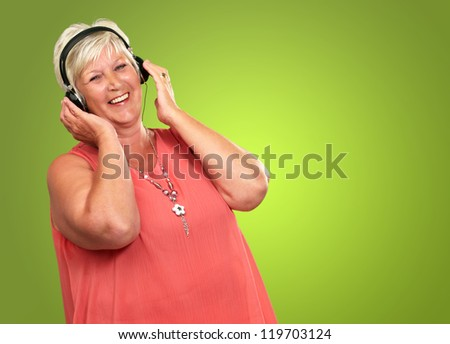 Portrait Of A Senior Woman With Headphone On Green Background - stock photo