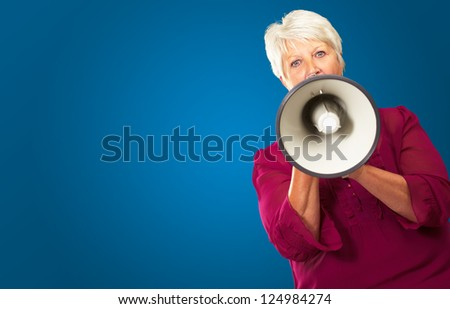 Portrait Of A Senior Woman With Megaphone On Blue Background - stock photo