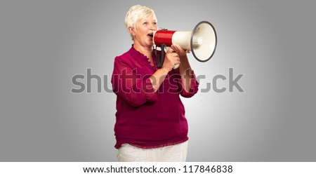 Portrait Of A Senior Woman With Megaphone On Gray Background