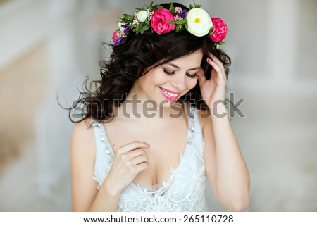 Portrait of a sensual beautiful brunette girl with a wreath of flowers on her head, cute smiling with closed eyes - stock photo