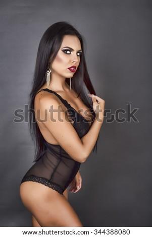 Portrait of a sensual brunette woman posing in sexy black lingerie.Studio shot - stock photo