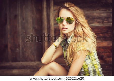 Portrait of a Sensual Fashion Hipster Girl on Wooden Background. Beautiful Blonde Woman in Sunglasses Outdoors. Street Style Female. Vintage Toned Photo with Copy Space.