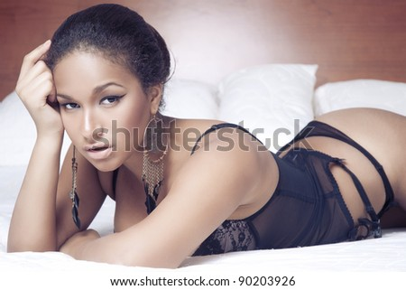 Portrait of a sensual sexy african woman lying on the bed in black lingerie - stock photo
