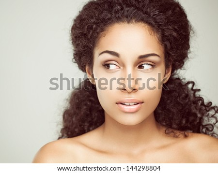 Portrait of a sensual young African woman casting a sideways glance. - stock photo
