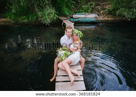 Portrait of a sensual young couple hugging on a wooden bridge on a background of blue water, lifestyle, love, romance, relationships