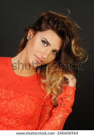 portrait of a sensual Young latin beautiful girl holding her long hair up and looking with an attitude straight at the camera on black background - stock photo