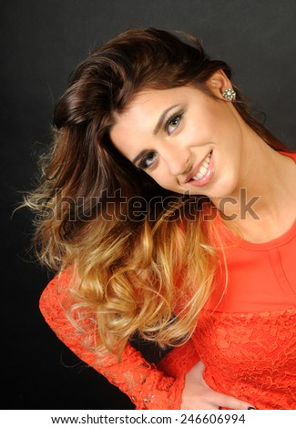 portrait of a sensual Young latin beautiful smiling and looking straight at the camera with her long hair in an artistic mess up if she were just woke up on black background - stock photo