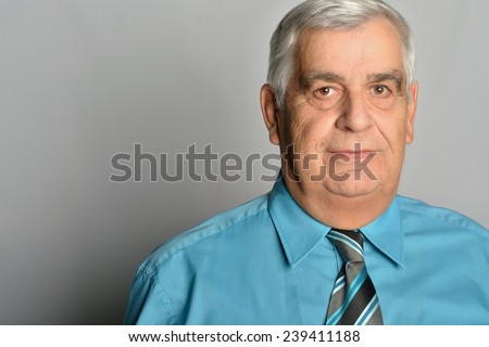 portrait of a septuagenarian with white hair, wearing a blue shirt and tie - stock photo
