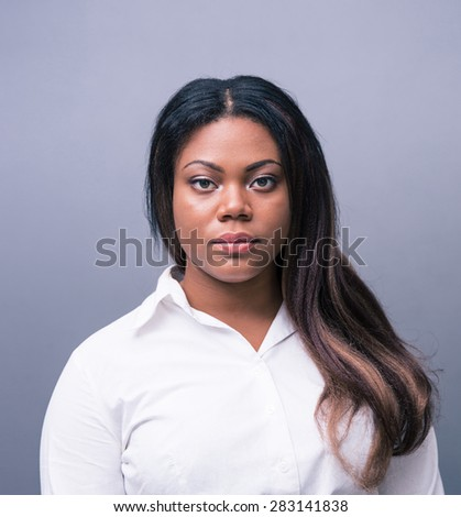 Portrait of a serious african businesswoman over gray background. Looking at camera - stock photo