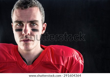 Portrait of a serious american football player looking at camera with black background - stock photo