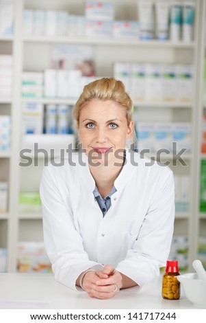 Portrait of a serious blond female pharmacist at drugstore - stock photo