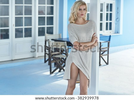 Portrait of a serious blonde standing on a hotel terrace