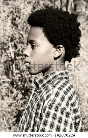 portrait of a serious boy with a cool hairstyle in autumn - stock photo