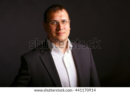 Portrait of a serious businessman on dark background - stock photo