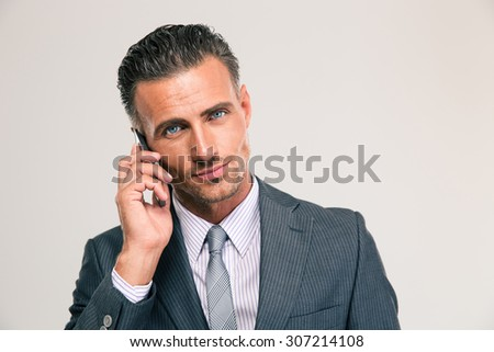 Portrait of a serious businessman talking on the phone isolated on a white background. Looking at camera - stock photo