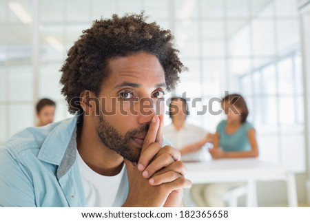 Portrait of a serious businessman with colleagues in meeting in background at the office - stock photo