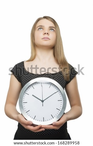 Portrait of a Serious Caucasian Teenage Girl Holding Office Clock. Isolated over White Background. Vertical Image - stock photo