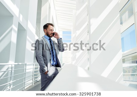 Portrait of a serious confident man boss having mobile phone conversation while resting after meeting with his partners, businessman talking on cell telephone while standing in modern space indoors - stock photo