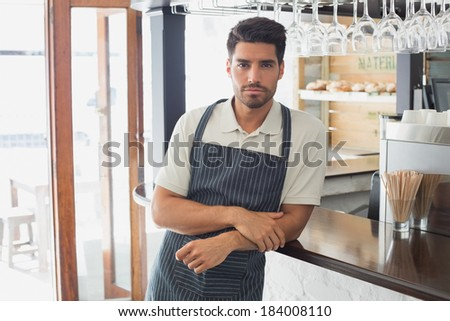 Portrait of a serious confident young waiter standing at the cafe counter - stock photo