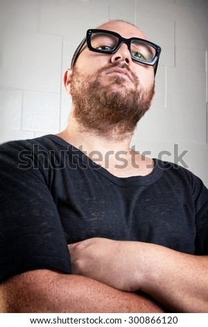 Portrait of a serious guy with a beard. Portrait of a casual dressed guy with arms crossed, who looks at you with superiority through his glasses. Portrait over textured background. - stock photo