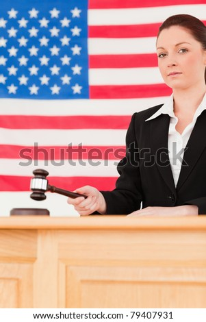 Portrait of a serious judge knocking a gavel with an American flag in the background - stock photo