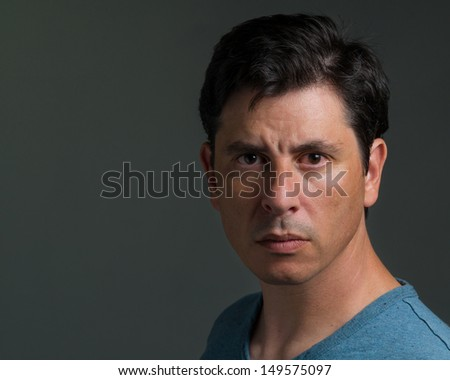 Portrait of a serious looking Caucasian man in his late thirties. He has dark short hair and a bloodshot eye