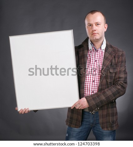 Portrait of a serious male holding blank white card on a gray background