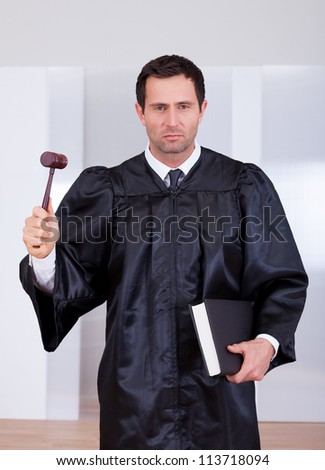 Portrait Of A Serious Male Judge Holding The Gavel And Book - stock photo