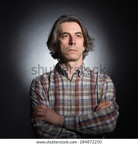 Portrait of a serious man aged 40-50 years on a dark background. - stock photo