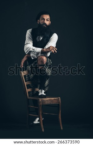 Portrait of a Serious Man with Long Beard Looking Afar, Holding a Cigarette with One Foot on Chair. Captured in Studio with Black Background.