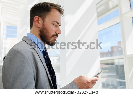 Portrait of a serious managing director dressed in elegant suit reading message on mobile phone during work break, young businessman concentrated looking at cell telephone while rest after conference  - stock photo