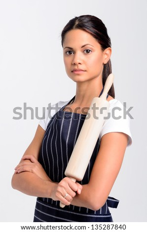Portrait of a serious professional baker holding a rolling pin, isolated on grey background - stock photo