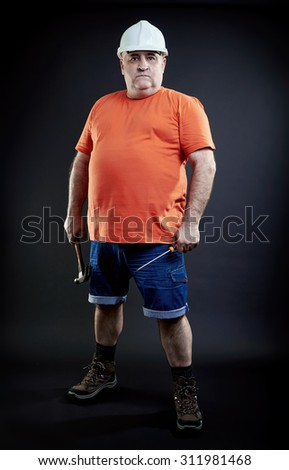 Portrait of a serious repairman wearing safety equipment holding hammer and screwdriver. Industry equipment concept. Full length. - stock photo