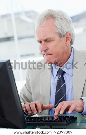 Portrait of a serious senior manager using a computer in his office