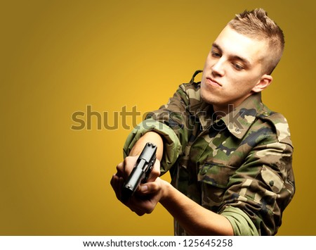 portrait of a serious soldier aiming against an orange background - stock photo