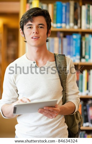 Portrait of a serious student holding a tablet computer in a library